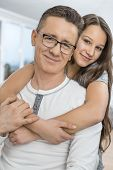 Portrait of affectionate girl embracing father from behind at home poster