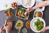 Convenient takeaway takeout food for party, overhead spread of assorted food with hands serving up poster