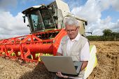 stock photo of threshing  - Farmer in wheat field with harvester - JPG