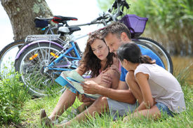 stock photo of family vacations  - Family on bicycle ride in the countryside - JPG
