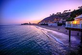 Scenic Coastal Landscape With Santa Monica Mountains And Surfrider Beach At Dusk Iluminated By Night poster