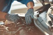 Close-up Of Automobile Mechanic In Gloves Examining And Repairing Car In Automobile Store poster