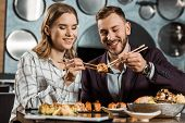 Smiling Attractive Young Adult Couple Eating Sushi Together In Restaurant poster