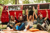 Group of friends hippies men and women rejoicing and sitting near vintage minivan into the nature poster
