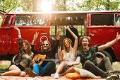 Group of young hippies men and women laughing and sitting near vintage minivan into the nature poster