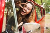 Photo of beautiful hippie girl smiling and showing peace sign while driving retro minivan in forest poster
