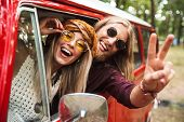 Photo of happy hippie couple smiling and showing peace sign while driving retro minivan in forest poster