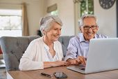 Happy smiling retired couple using laptop at home. Cheerful elderly man and old woman using computer poster