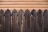 Pointed Wooden Fence On Backdrop Of House With Surface From Siding. Background Image Of Wooden Fence poster