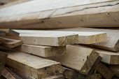 Close-up Of Piled Stack Of Natural Brown Uneven Rough Wooden Boards Lit By Bright Sun. Industrial Ti poster