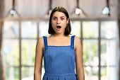 Happy Surprised Woman On Blurred Background. Pretty Short Hair Girl Standing With Mouth Open In Surp poster