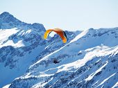 foto of ultralight  - A flying paraglider in mountains in the winter - JPG