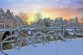 City scenic from Amsterdam in winter in the Netherlands at sunset poster