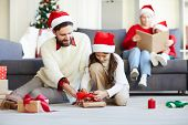 Little Santa girl tying up knot on top of packed giftbox while father helping her poster