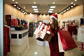 Happy Girl Shopping Gifts In Mall On Christmas Sale. New Year Holidays Shopping Idea Concept. Smilin poster