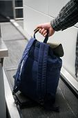 Mans Hand With A Backpack On Luggage Conveyor Belt System At Check In Desk In Airport. Blue Backback poster
