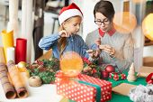 Young woman looking in open giftbox while preparing xmas surprises with her little daughter poster