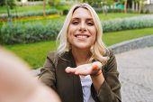 Image of charming woman 20s wearing jacket smiling and taking selfie photo while walking through par poster