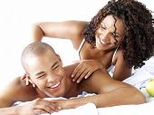 Happy afro american couple on bed.  Latin couple on bed.