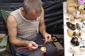 Sorochinskaya Fair.  Man Decorates Crafts.