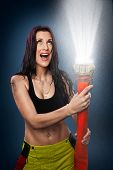stock photo of firehose  - Young woman spraying water in the air with a fire hose - JPG