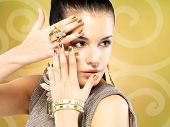 image of minx  - Pretty woman with golden nails and beautiful gold ring over creative background - JPG