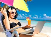 stock photo of sunbathing woman  - Happy woman on the beach with a laptop computer - JPG