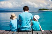 stock photo of sisters  - Back view of father and kids sitting on wooden dock looking to ocean - JPG