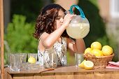stock photo of pitcher  - little girl drinking from lemonade pitcher at her lemonade stand - JPG