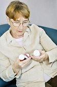 picture of elderly woman  - Elderly woman reading warning labels on pill bottles with medication - JPG