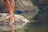 image of toe  - Woman on rock at beach dipping toes in water - JPG