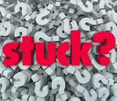 The word Stuck on a background of question marks to illustrate being caught in a sticky situation, p