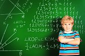 stock photo of schoolboys  - Portrait of a smiling schoolboy standing over blackboard - JPG