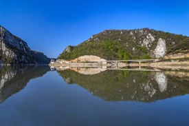 stock photo of decebal  - Danube Gorges reflecting in the Danube River Romania - JPG