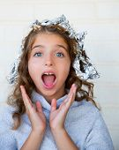Funny kid girl surprised with his dye hair with foil blue eyes