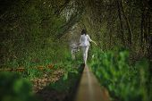 stock photo of girl walking away  - photo of a girl running away on the rails in nature - JPG