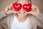 stock photo of corazon  - Image of smiling female with two red hearts by her eyes - JPG