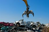 stock photo of junk-yard  - Crane picking up crushed cars in a junkyard - JPG