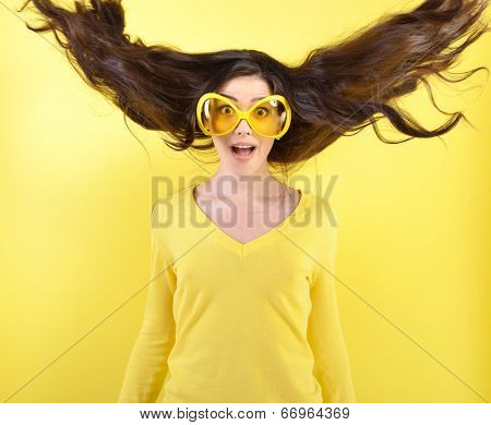 Joyful excited surprised young woman with flying hair and big funny glasses over yellow background.  poster