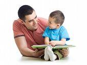 stock photo of nurture  - kid boy and his dad read a book - JPG