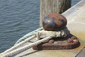 image of bollard  - A bollard in a harbor with a thick rope to fasten a ship - JPG
