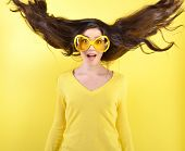 image of hair blowing  - Joyful excited surprised young woman with flying hair and big funny glasses over yellow background - JPG