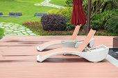 stock photo of lawn chair  - Wicker deck chair and table in the beautiful summer park with green lawns and flowerbed - JPG
