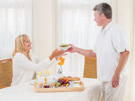 picture of table manners  - Mature senior husband serving his wife healthy breakfast passing her a bowl of cereal off the tray laden with fresh fruit eggs baguette and coffee as she sits at the dining table - JPG