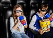 stock photo of watching movie  - Sisters having snacks while watching 3D movie at cinema theater - JPG
