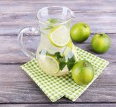 stock photo of pitcher  - Lemonade in pitcher on wooden background - JPG