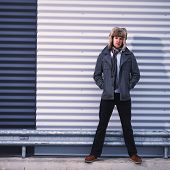 stock photo of overcoats  - Fashionable young man wearing fur hat and warm overcoat corrugated iron wall on background  - JPG