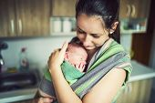 foto of mother-in-love  - Newborn baby hold by mother in the baby wrap carrier.