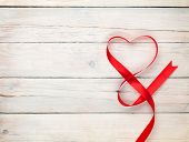 stock photo of wooden table  - Valentines day background with heart shaped ribbon over white wooden table background - JPG