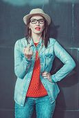 foto of middle finger  - Young beautiful girl in red jersey and hat showing middle finger outdoor near wall - JPG